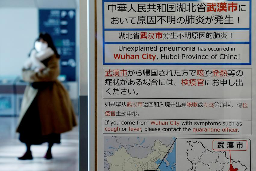 A woman wearing a mask walks past a quarantine notice about the outbreak of coronavirus in Wuhan, China at an arrival hall...