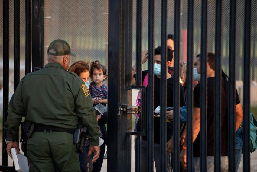 A group of migrants wait to turn themselves over to National Guard and Customs and Border Patrol officials at the U.S. and M…