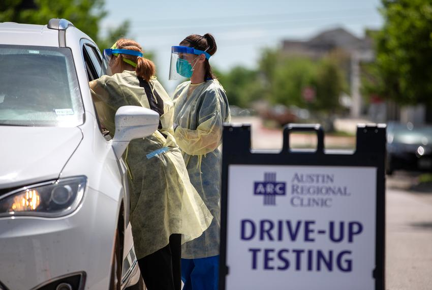 Nurse Kristen Howell, left, and Medical Lab Tech, Amanda Hernandez, administer a COVID-19 test at the Austin Regional Clinic…