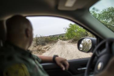 Border Patrol Agent José Perales examines tracks on an unpaved gravel road while looking for unaccompanied child migrants and families crossing from Ciudad Miguel Alemán, Mexico, to Roma, Texas. Unlike undocumented adult migrants, unaccompanied children and families ordinarily turn themselves in to U.S. law enforcement.