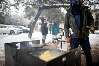 Josh Olszewski cooks eggs over a a grill after his apartment lost power due to the severe winter storm that hit the state. Feb. 18, 2021.