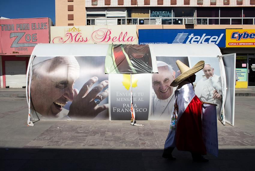 A man in a sombrero and draped with the Mexican flag is seen walking near a Pope Francis display in the center of Ciudad Juá…