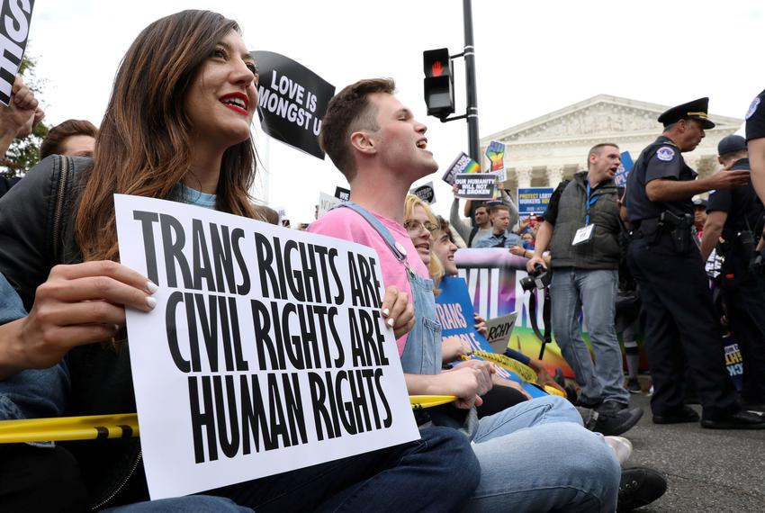 LGBTQ activists and supporters blocked the street outside the U.S. Supreme Court as it heard arguments in a major LGBTQ righ…