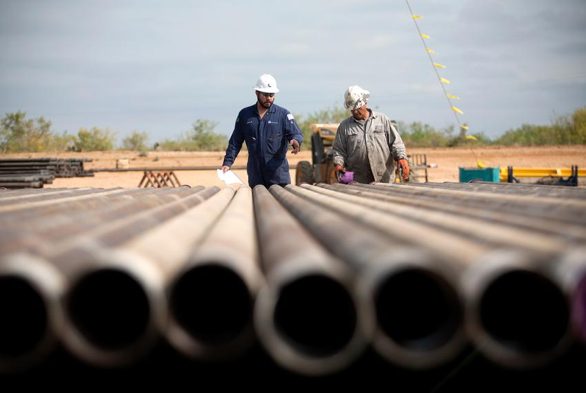 Rig workers inspect casings that will be loaded into the well in preparation for the hydraulic fracturing process at a Chesa…
