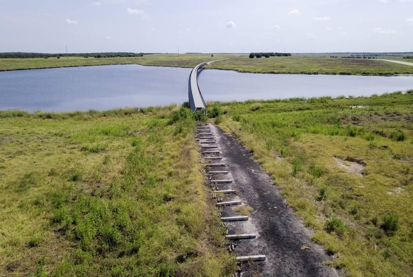 A conveyor belt runs over a lake on the grounds of the Alcoa Mine near Rockdale on Aug. 1, 2019.