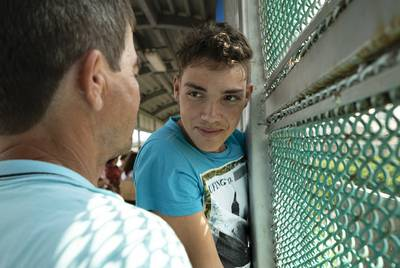 Washington Moreira Batista, 17, waits on the Brownsville/Gateway International Bridge with his father, Jose Moreira Nunez, 52, for their chance to apply for asylum in the United States.