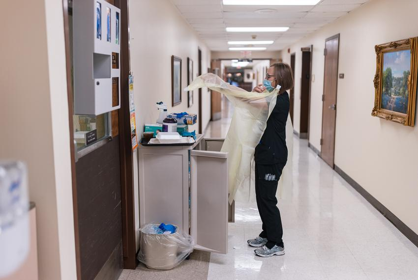 Registered Nurse Lori Kelley dons a surgical gown and other PPE before entering the room of a COVID-19 patient at Goodall-Wi…
