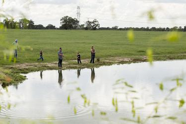 Randa and Charlie Calhoun with their twin sons, Cainen and Cash, 5, fish on their land in Bedias, Texas, on Sept. 15, 2018. The proposed high speed rail would be built along existing power lines.