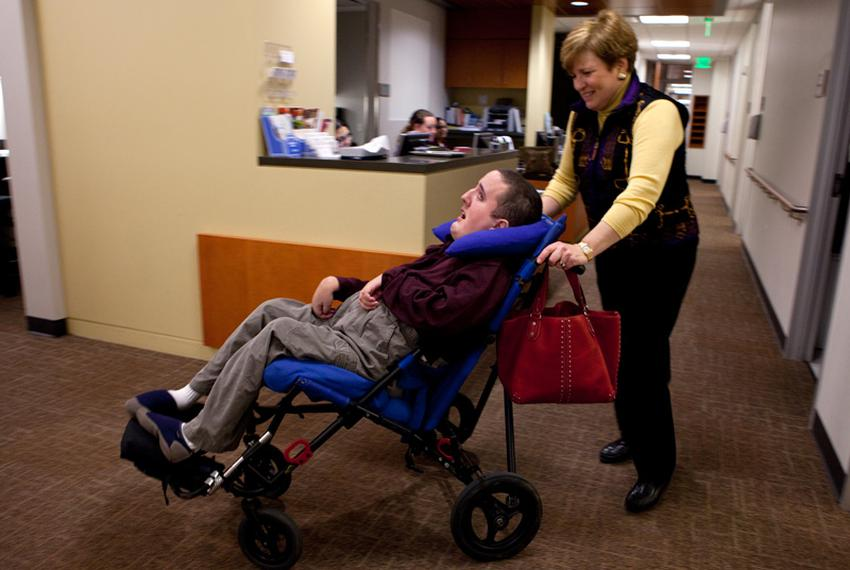 Ann Ligums pushes her profoundly disabled son Benjamin, 26, into the Baylor Transition Medicine Clinic in Houston.