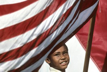 A young boy carries an American flag at a Juneteenth celebration in Austin.