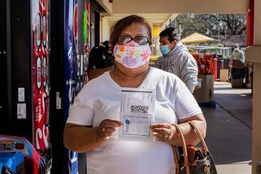 Maria Gilberta Reyna poses with her COVID-19 vaccine appointment information at a registration event in Irving on March 19, 2021.