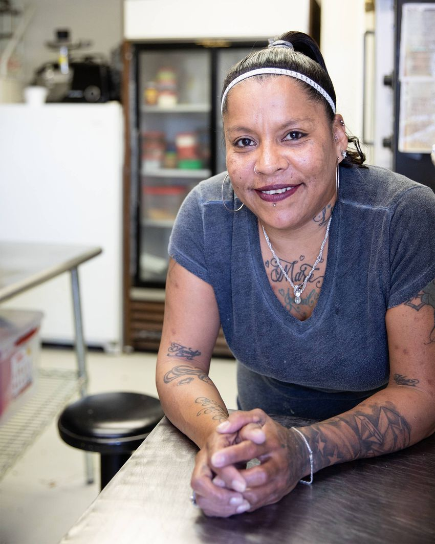 Francis Castillo poses for a portrait at the bakery where she works.  Castillo is homeless, living at the Hope Haven shelter…