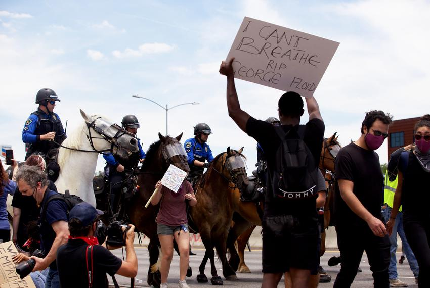 Police officers on horseback are among a crowd gathered to protest protest the deaths of George Floyd and Mike Ramos, in A...