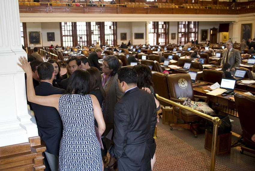 Democractic members huddle in the rear of the Texas House chamber while HB12 immigration bill is being negotiated on May 9, …