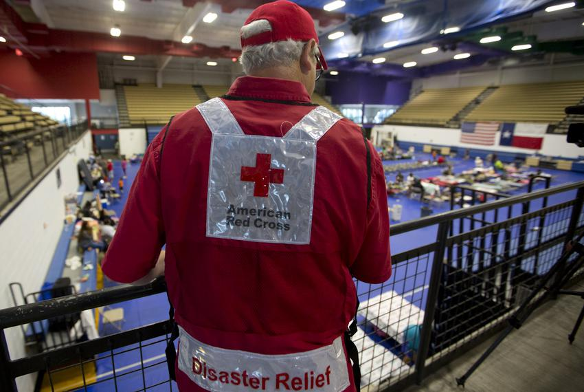 A Red Cross volunteer looks over the railing in a shelter where rows of cots have been set up for those seeking refuge from …