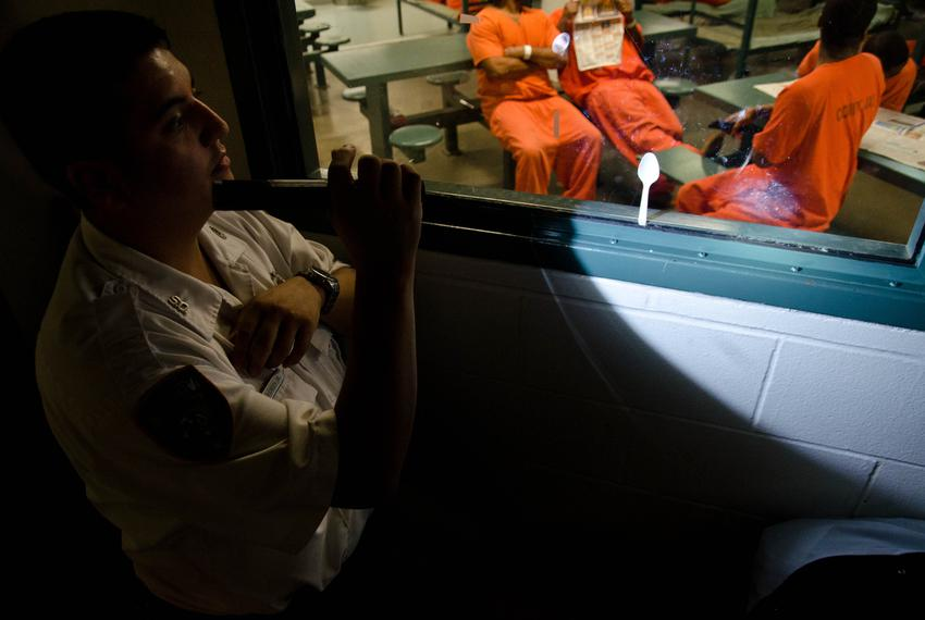 Detention officer watches over inmates from a control room inside the Harris County Jail.