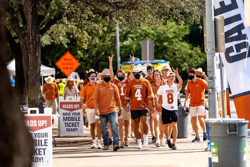 A group of students walks towards the stadium for the first home football game of the season at the University of Texas in A…