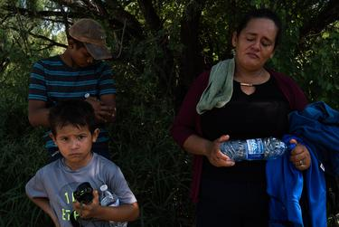 Doris Romero, 42, from Honduras, waits with her son, Jose, 14, and her nephew, Ronald, 4, wait to be processed after turning themselves in to U.S. Border Patrol agents, near McAllen on August 1, 2018.