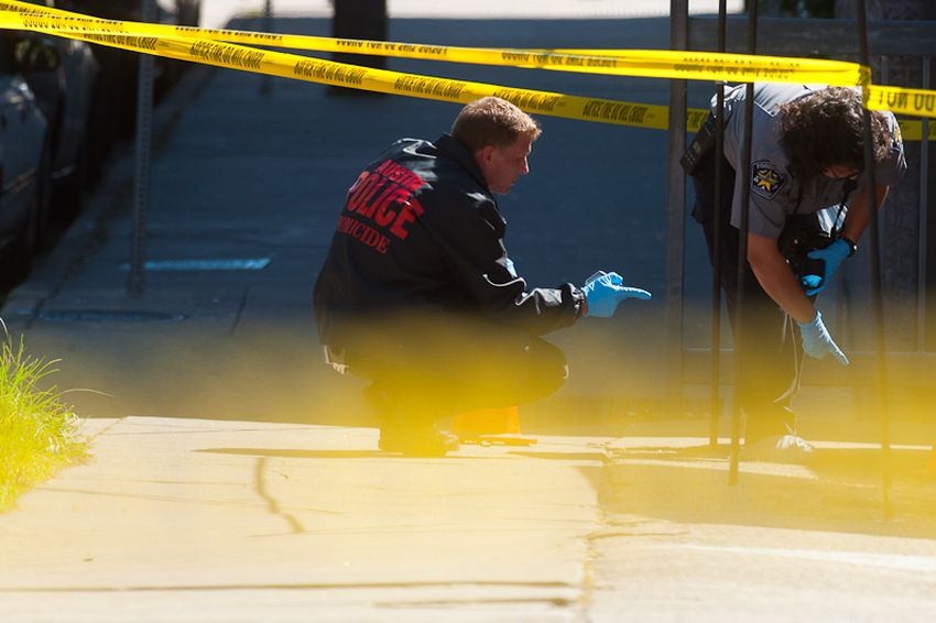 Forensic investigators from the Austin police department search the area for ejected casings from the suspect's AK-47.