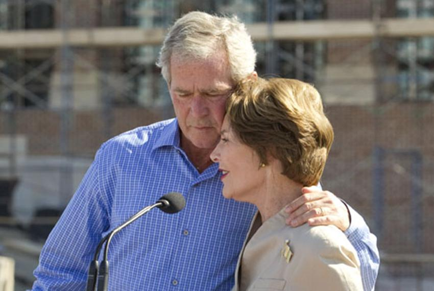 Former President George W. Bush hugs Laura Bush at the topping out ceremony for the George Bush Presidential Center at Sou...
