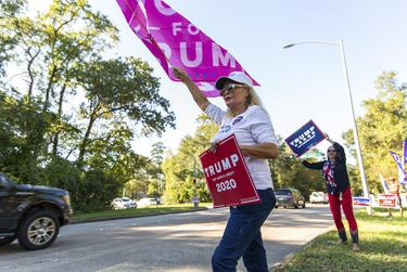 A Trump supporter waves a Women for Trump banner for motorists outside the Kingwood Community Center on Election Day.
