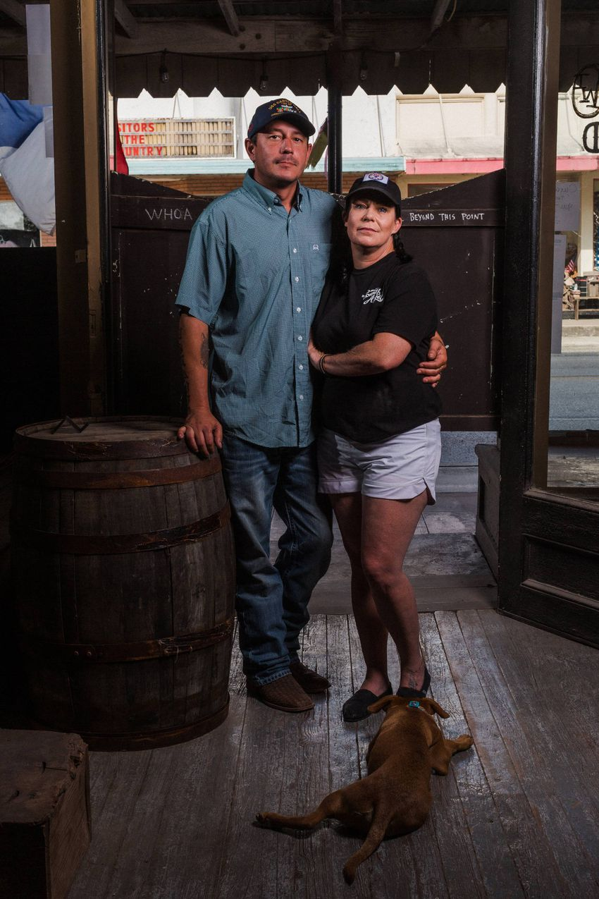 Elizabeth McNiel, the owner of Ironwood Saloon and an ASL teacher, her husband Ryan and their dog Rojo in their empty bar ...