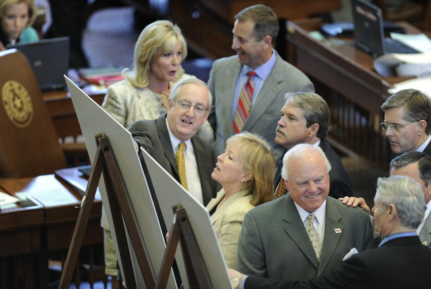 State representatives look at redistricting maps on the floor of the Texas House on April 27, 2011