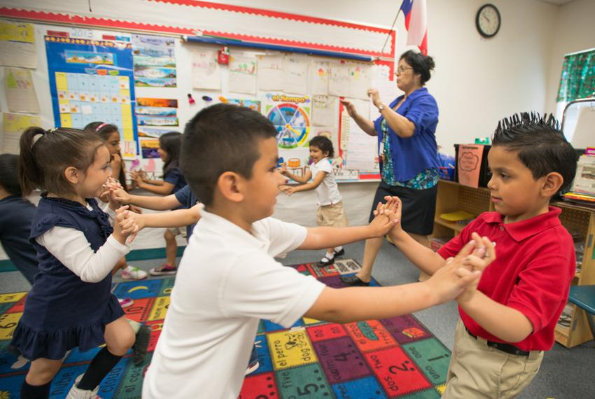 "Pre-K teacher Josefina Pineda teaches her students the concept of ""push"" by having them join hands and push back and forth..."