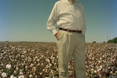 """Portrait of Pete Laney in a West Texas cotton field, 1998.  While photographing politicians, Newton said he was constantly on the lookout for ways to distill a whole array of information about a candidate's character and ideals into a single, appealing image.  In this shot, taken for Laney's re-election campaign, the then-Texas House speaker stands in a cotton field shortly after sunrise, surrounded by the primary crop of his district near his hometown in Hale County.  """"They grew cotton. That was his district, that's him,"""" Newton said. """"He was quite a leader. He manned the Alamo for the Democrats, essentially — when he went down that was the end of the Democrats in this state.""""  Laney, who was speaker from 1993 until 2003, when Republicans took the majority, was the last Democrat to hold that office. He had served in the House for more than three decades when he announced he would not seek re-election in 2006."""