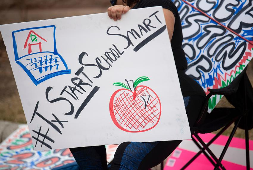 A teacher holds a sign outside the Capitol Grounds during the 'Mask Up, Line Up' teacher protest on July 15, 2020 in Austin.
