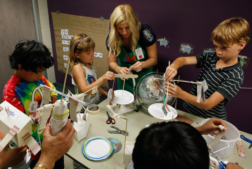 Austin Children's Museum volunteer Alyssa Guiliani helps kids finish their kinetic energy projects at a Secret Scientists ...