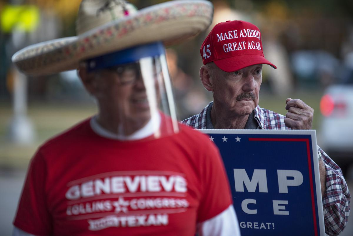 Jack Kennedy, right, sports a Make America Great Again cap while holding a Trump-Pence sign outside of the polling location at University Park United Methodist Church in Dallas on Nov. 3, 2020.