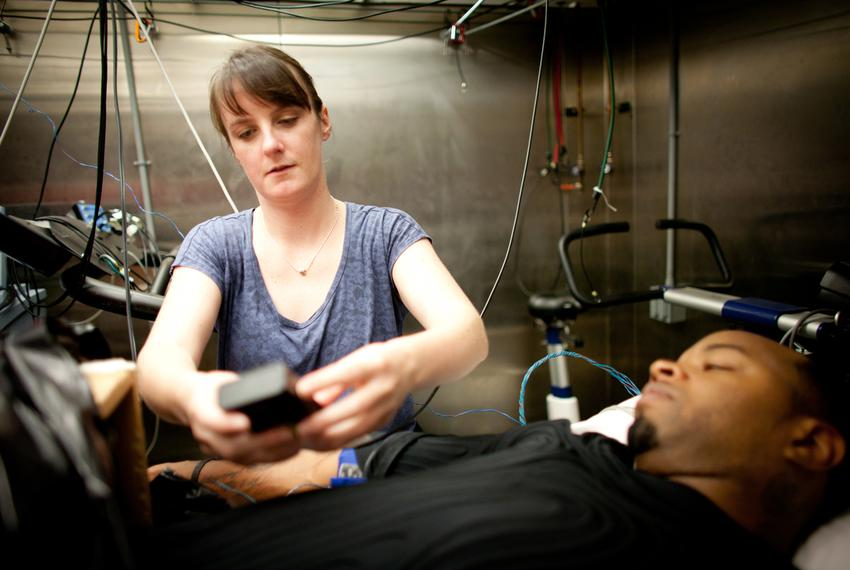Becky Lucas, post doctoral fellow, assists in the set up of the environmental chamber, Antionne Williams, 31, volunteer re...