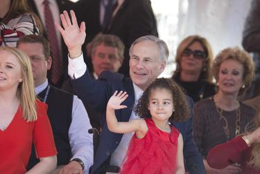 Chrisma Boone sits on the lap of her uncle, Gov. Greg Abbott, as they watch the inaugural parade on Congress Avenue.