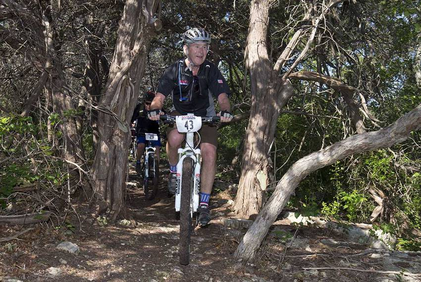 Former President Bush leads the way through a stand of cedar trees on his ranch near Crawford during his annual W100K ride...