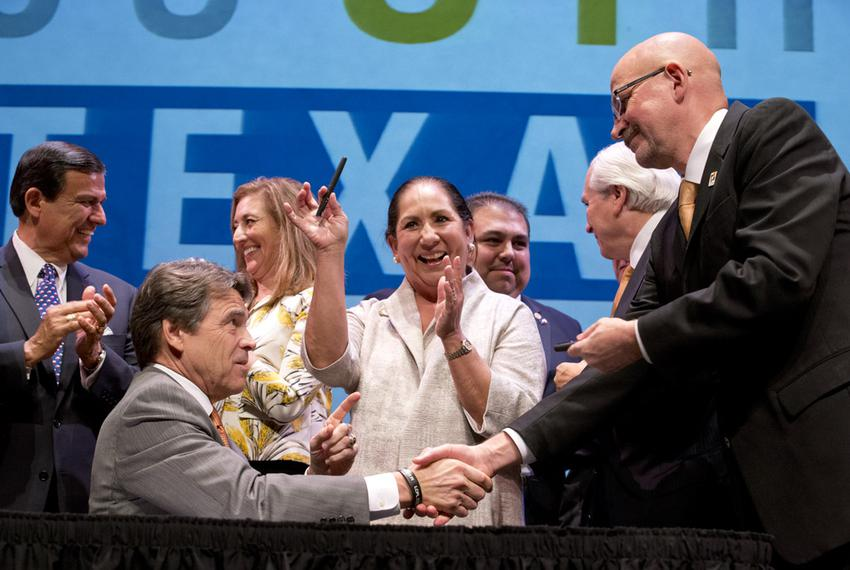 UT-Brownsville President Dr. Juliet Garcia shows off one of the pens that Texas Governor Rick Perry used to ceremonially sig…