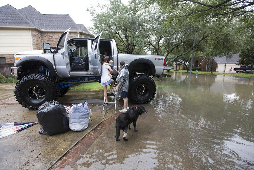Chris Ginter, right, helps a family into his truck in Houston on Tuesday, Aug. 29, 2017. Ginter is helping evacuate people f…