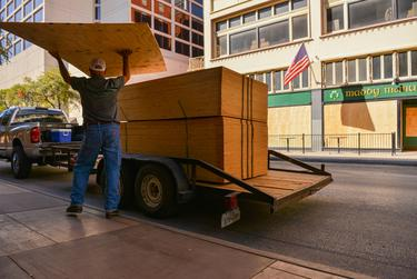 A worker unloads sheets of plywood to board up a downtown San Antonio building in the event of civil unrest as a result of the election.
