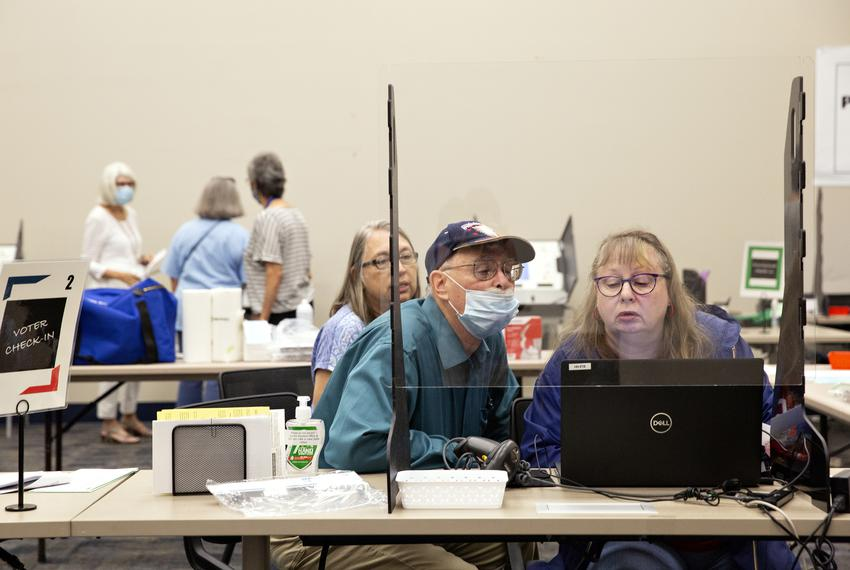 Poll workers Al Johnston and Sue Denson run through the check in process at training lab at the Collin County Elections Depa…