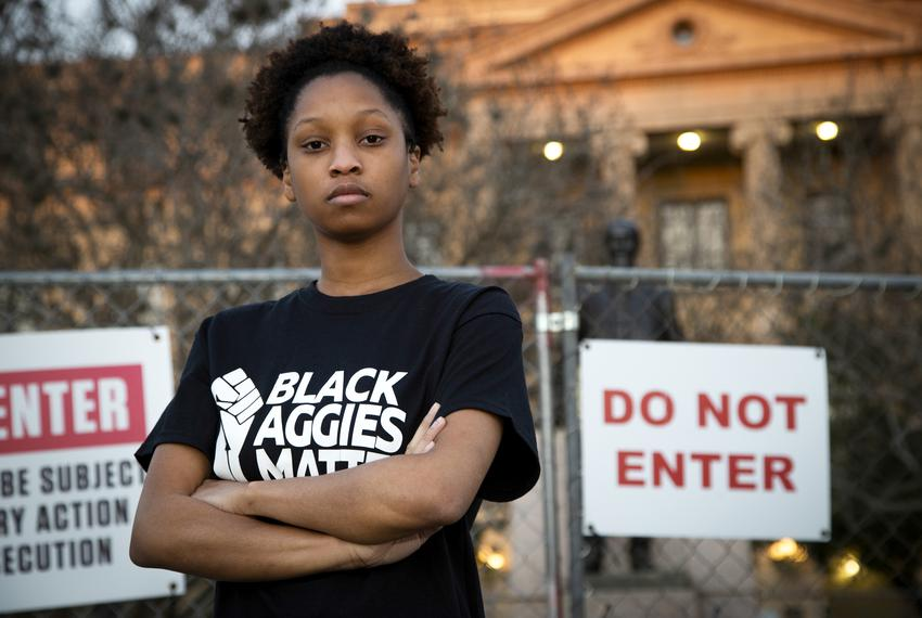 Qynetta Caston, a student at Texas A&M University, stands in front of a fenced-in statue of former college president Lawrenc…