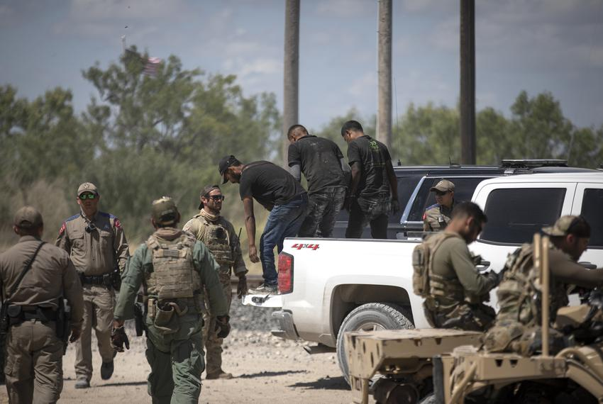 A group of migrants walk off a pick-up truck after being apprehended by Department of Public Safety officers at a train depo…