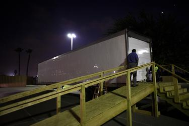 Juan Lopez waits to pick up a body from a refrigerated trailer at Doctors Hospital at Renaissance in Edinburg.