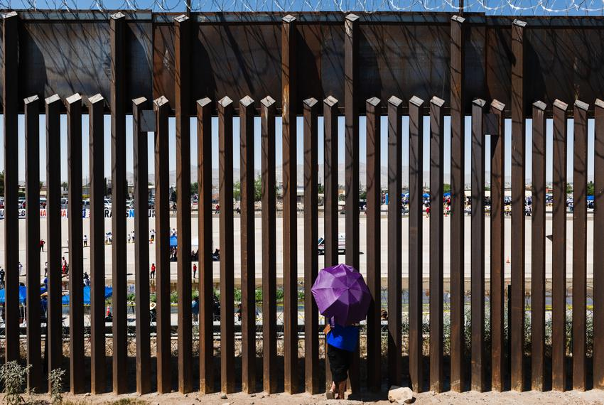 A woman looks through the border wall towards her family in Ciudad Juarez, Mexico from El Paso, Texas on June 19, 2021.