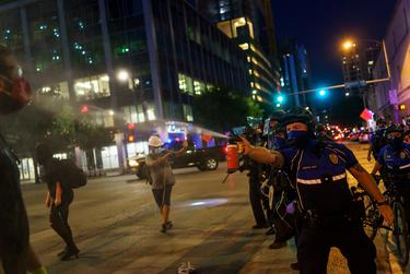 A police officer sprays a protester with pepper spray as protestors clashed with police in riot gear in downtown Austin on Aug. 1, 2020.