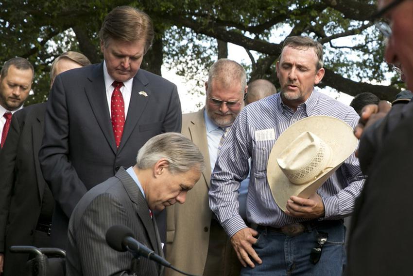 Jason Taylor from the Barnone Cowboy Church prays after Gov. Greg Abbott signed Senate Bill 2065, the Pastor Protection Bill…