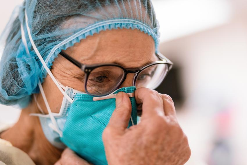 Registered Nurse Lori Kelley dons an N95 mask and other PPE before entering the room of a COVID-19 patient at Goodall-Witche…