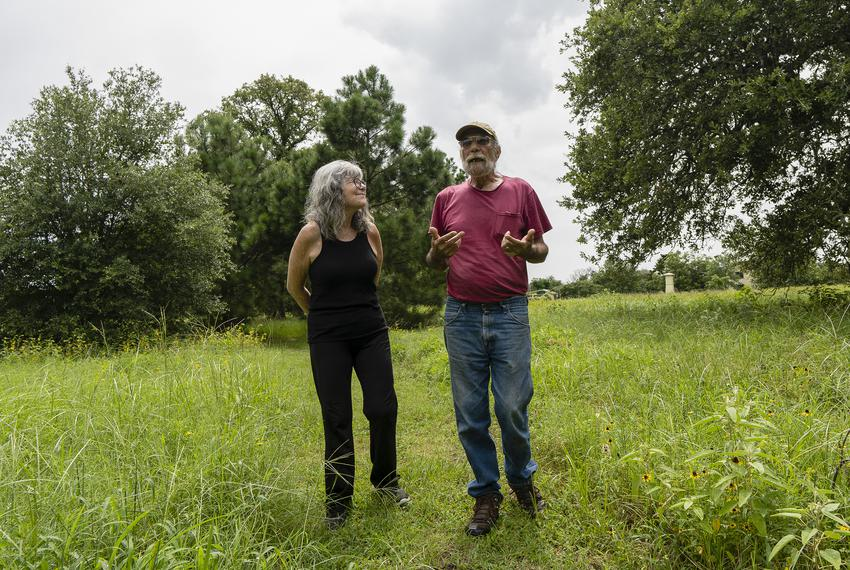 From left, Leslie Scouras, 63, and her husband Bob Scouras, 72, walk a path on their property in Lee County on July 12, 2021…