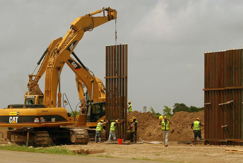 A construction crew works to erect a portion of the border wall along Oklahoma Ave. south of Brownsville on June 9, 2009. ...