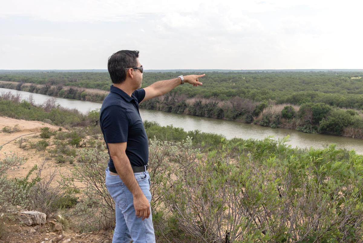 Gerardo Vargas points towards the land on the Mexican side of the Rio Grande River. June 23, 2021.