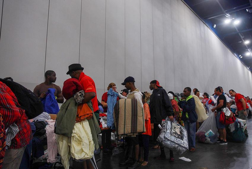 Evacuees seeking shelter from flooding wait in line to get into the George R. Brown Convention Center in Houston on Sunday...